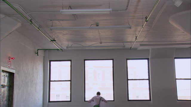 Wide shot man looking out window in empty loft/ turning around and punching air in excitement and walking toward camera/ Brooklyn, New York