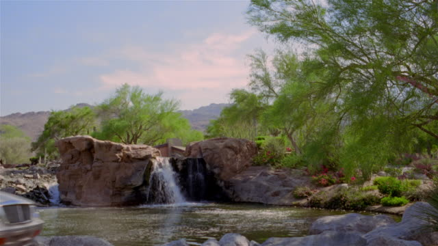 Wide shot man riding golf cart past waterfall and stream