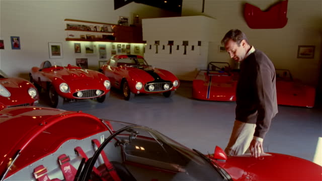 Wide shot man running his hands along the side of red sportscar in garage