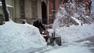 Wide shot man using snow blower in front of apartment buildings / Brooklyn