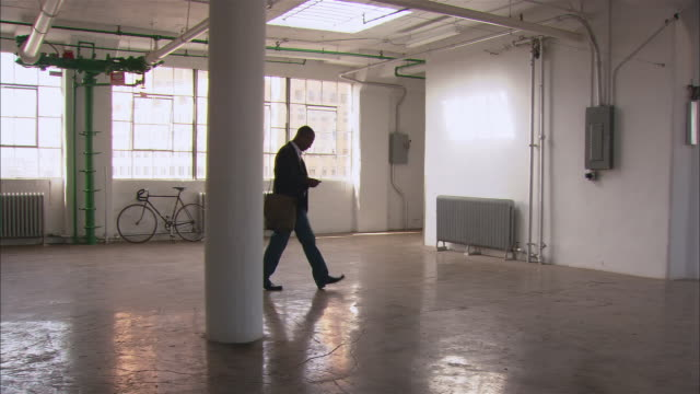 Wide shot man walking across empty loft space while dialing number on mobile phone/ man removing shoulder bag and crouching down to talk on phone/ Brooklyn, New York