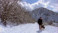 Wide shot man walking up snowy mountain path w/dog / Colorado