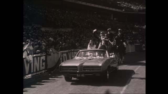 wide shot MCG grandstand ansd scoreboard / Shane Gould walking through the crowd with officials wearing Olympic uniform and followed by other unknown...
