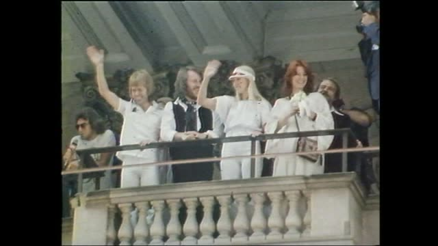wide shot Melbourne Town Hall with fans in front / ABBA Agnetha Faltskog Bjorn Ulvaeus Benny Andersson and AnniFrid Lyngstad stand on the balcony...