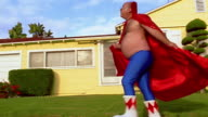 Wide shot middle aged man in superhero cape and tights skipping from suburban house to 1950s car