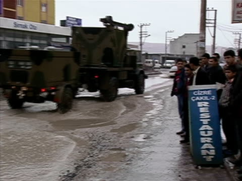 Wide shot Military convoy driving through city past pedestrians and spectators/ Cizre Mardin Province Turkey