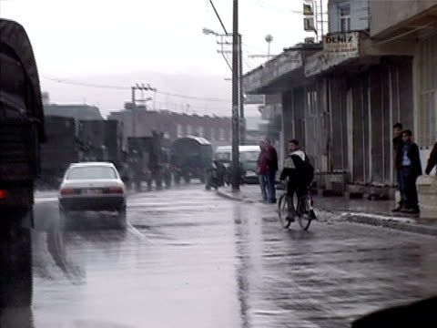 Wide shot Military convoy driving through city past pedestrians/ Cizre Mardin Province Turkey