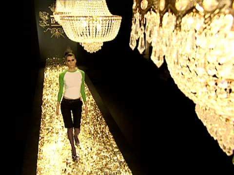 Wide shot Models parading down catwalk below chandelier during B&C European Style fashion show rehearsal/ Belgrade, Serbia