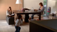 Wide shot mother working on laptop, daughter reading book and son playing with toy on floor in home office
