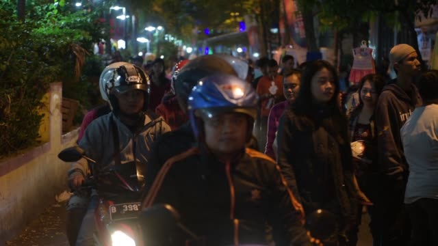 Wide shot motorcyclists drive past clothing stalls Medium shot a blue taxi drives past pedestrians and clothing stalls