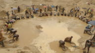 Wide shot of a large group of men panning for diamonds in a diamond mine pit in Sierra Leone.