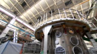 Wide shot of a new nuclear fusion device at a laboratory followed by a closeup of sparks on the machine