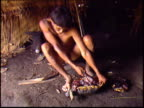 A wide shot of a Yanomami Indian man slaughtering a turtle inside a traditional Maloca dwelling