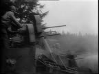 Wide shot of armored vehicle with two soldiers on top driving down a road in a heavily wooded area / camouflaged tank hauling a Bofors artillery...
