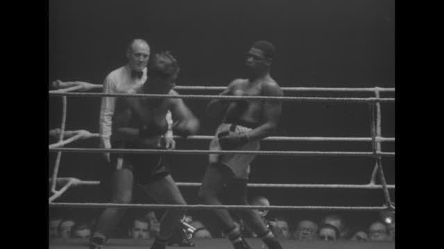 Wide shot of boxer in ring surrounded by crowd / Max Schmeling in audience / men battle it out in ring / man wearing ascot / Neuhaus beaten by Valdes...