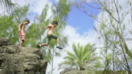 Wide Shot of Boy Jumping a Rock Crevace in Slow Motion