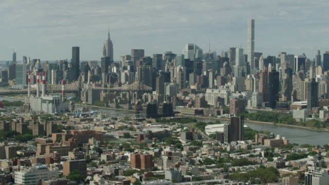 Wide shot of buildings with the Queensboro Bridge and Manhattan buildings in the background