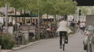 Wide shot of busy city sidewalk restaurant and street / Berlin, Germany