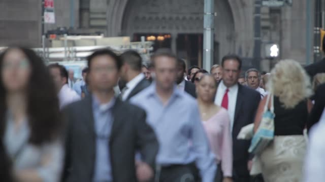 Wide shot of commuters walking down a busy sidewalk in the financial district of downtown Manhattan New York on July 2nd 2015 Shots