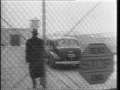 Wide shot of corner street scene in New York / Shot of crowd waiting outside a jail / Close up shot of Louis 'Lepke' Buchalter hiding his face as his...