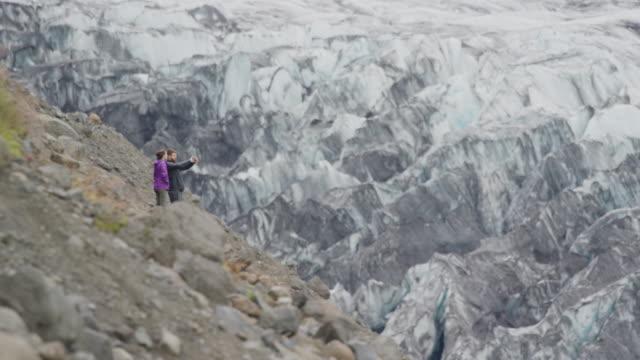 Wide shot of couple photographing ice on mountain range / Austur-Skaftafellssysla, Iceland
