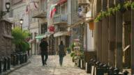 Wide shot of couple walking on cobblestone street / Veliko Tarnovo, Bulgaria