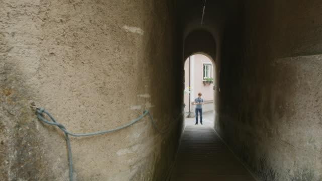Wide shot of distant tourist photographing tunnel / Hallstatt, Austria
