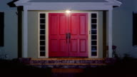 Wide shot of double front doors of suburban house at night / lights turning on inside house / Santa Barbara, California
