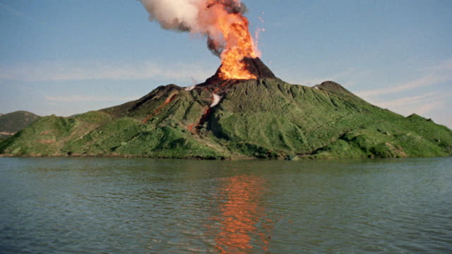 wide shot of erupting volcano / lake in foreground