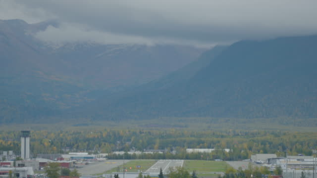 Wide shot of forested mountains with Merrill Field airport in the foreground