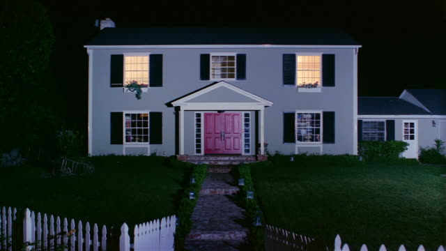 Wide shot of front of suburban house at night / lights turning on in rooms / lights turning off / Santa Barbara, California