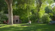 Wide shot of girl swinging on rope swing / Springville, Utah, United States