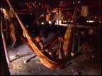 A wide shot of hammocks inside a traditional Maloca dwelling