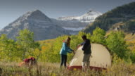 Wide shot of hikers assembling camping tent near mountain / American Fork Canyon, Utah, United States