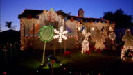Wide shot of house w/Christmas display in front yard at night / Burbank, California