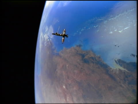 wide shot of MIR space station flying in outer space above Earth / STS79