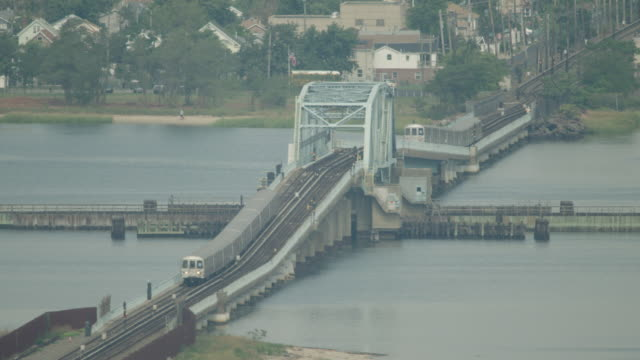 Wide shot of NYC subway 'A' trains moving over a hump bridge in Queens