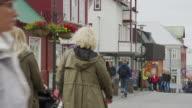 Wide shot of people walking in busy city / Reykjavik, Iceland