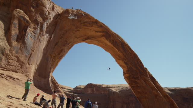 Wide shot of people watching man swinging from arch / Corona Arch, Moab, Utah, United States