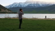 Wide shot of Photographer at mountain lake