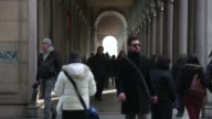 Wide shot of road in central Turin cars driving past Pedestrians walking down shopping arcade Turin city street scenes on January 29 2013 in Turin...