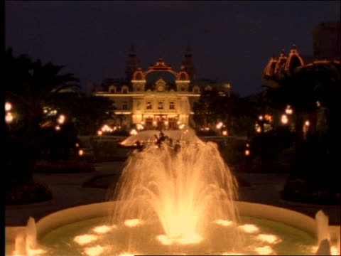 wide shot of Royal Palace with fountain in foreground at dusk / Monaco