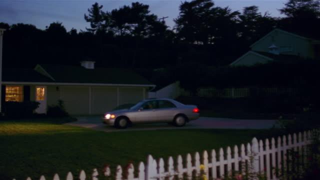 Wide shot of sedan pulling into driveway at night / pan to front of suburban house with lights on / Santa Barbara, California