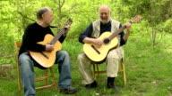 Wide Shot of Senior Men Playing Guitar and Singing