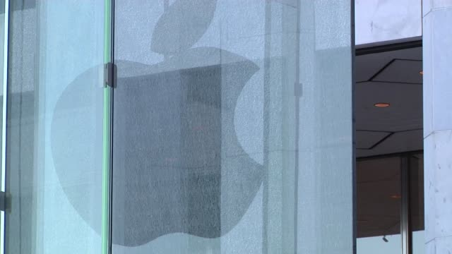 A wide shot of the Apple Flagship Store in New York New York with a broken glass pane in the façade A tight shot of the Apple logo reflecting in the...