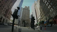 Wide shot of the financial district in New York City with sculptures.