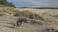 Wide shot of two girls riding on horses