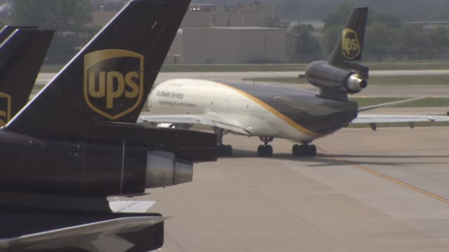 A wide shot of two UPS Worldwide Service airplanes parked at the gate at the UPS Worldport on an overcast day in Louisville Kentucky Medium shots of...