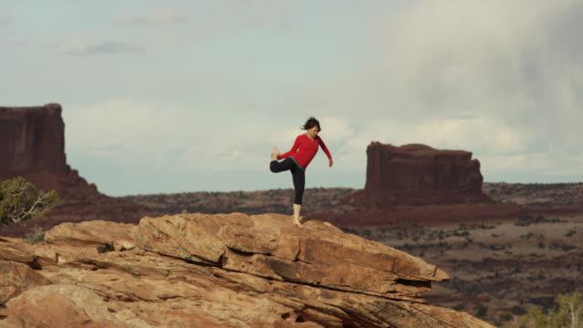 Wide shot of woman doing yoga on mountain / Moab, Utah, United States