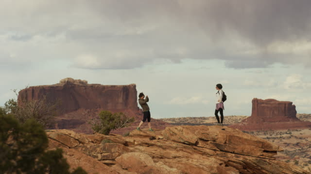 Wide shot of women posing on mountain with scenic view / Moab, Utah, United States